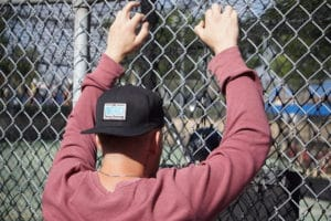 man hangs on to chain-link fence thinking about men's sober living homes