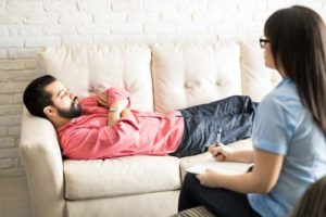 A therapist talks to a man about cognitive behavioral therapy