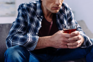 man sitting on couch with drink in hand thinking about being a high-functioning alcoholic