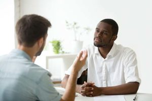 man listening to explanation about a Men's Rehab Program