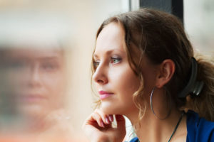 young woman staring out the window wondering What Is Drug Detox