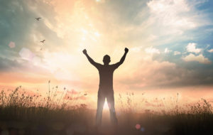 man raising arms in celebration of national recovery month