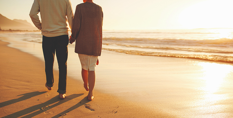 an image of people walking on a beach discussing how to rebuild relationships after rehab