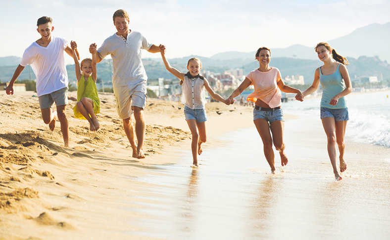 an image of a family running on the beach after discussing rehab for teens