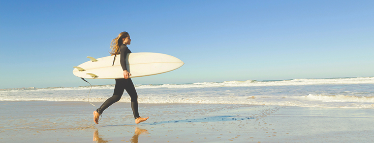 an image of a women surfing, an activity she found in her life after addiction