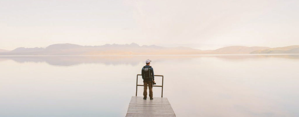 an image of a person in front of a lake, pondering dual diagnosis recovery