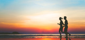 an image of two people running on the beach after going to a California rehab for club drugs